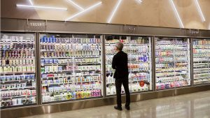 A shopper stands in front of a Whole Foods dairy display deciding which healthy products to purchase