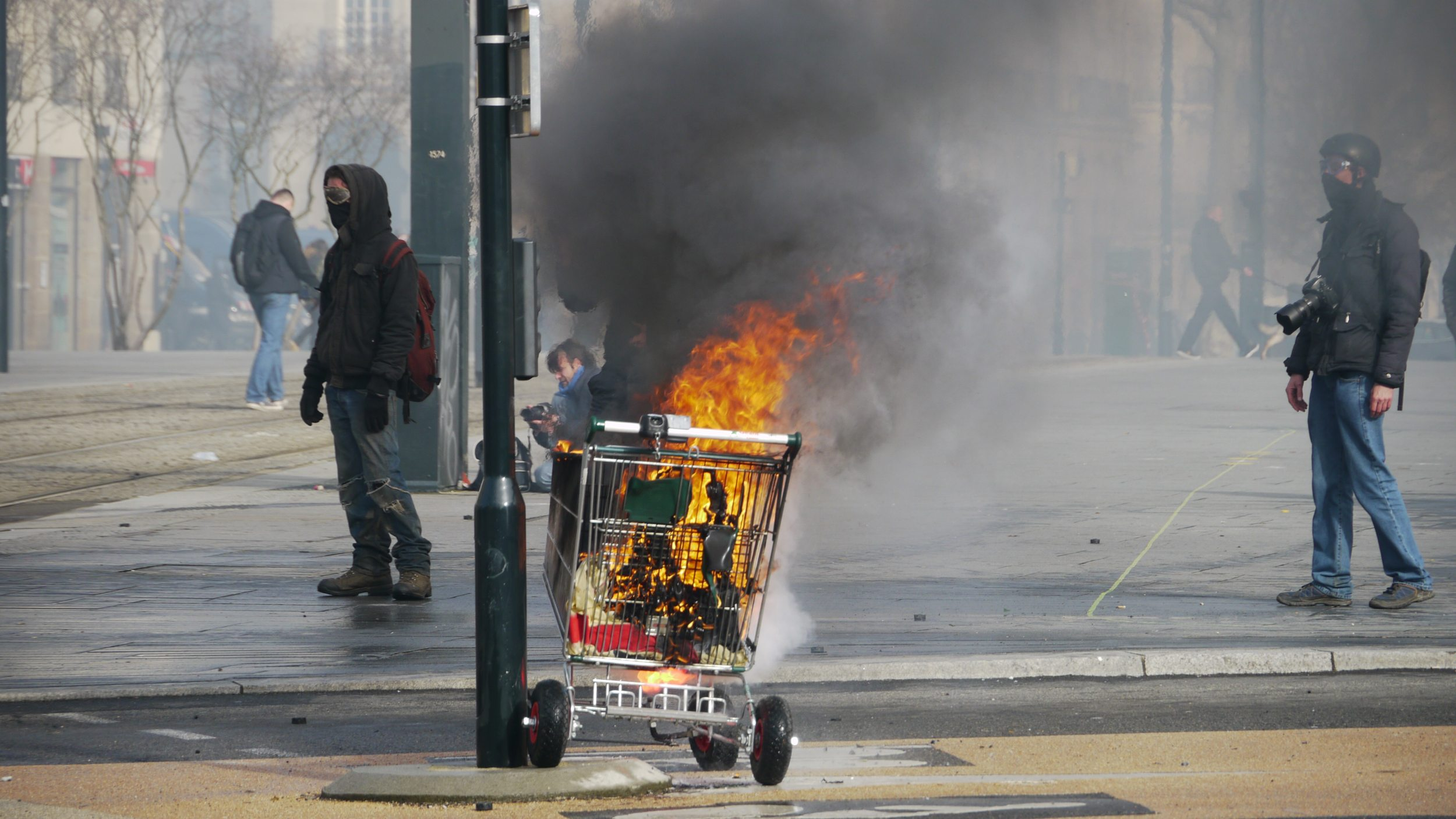 Burning shopping cart on rioting streets