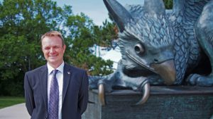 Professor Evan Fraser stands in front of the Gryphon statue