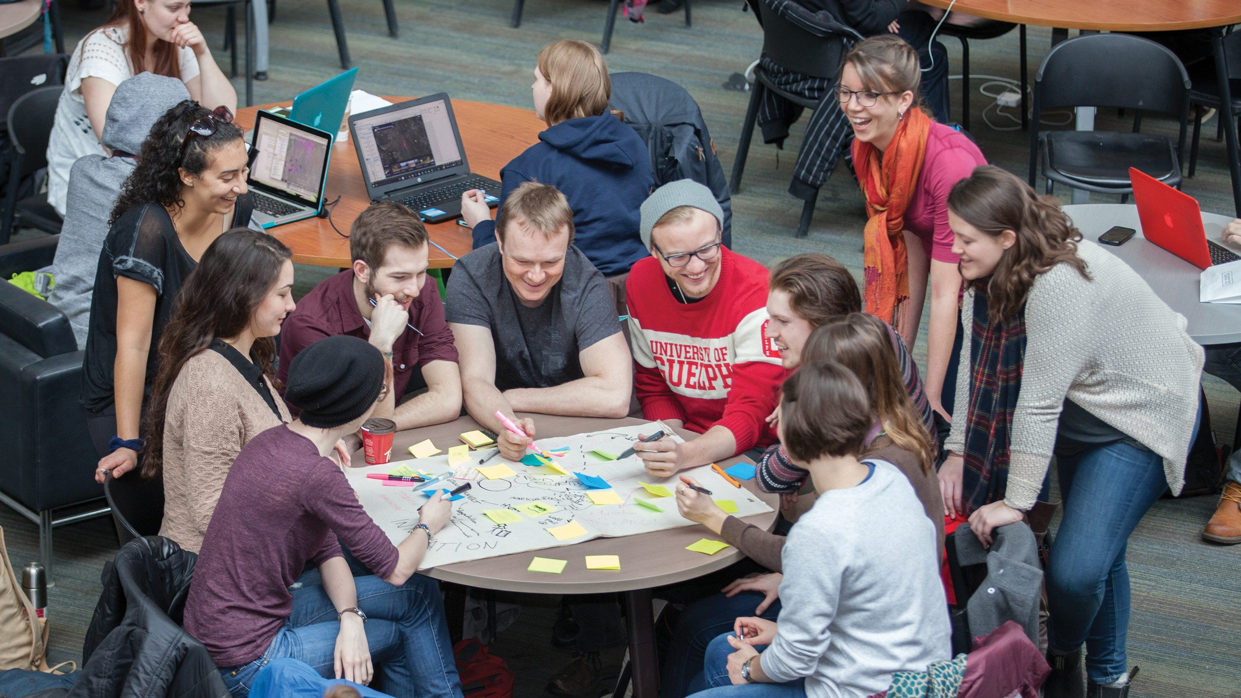 Evan Fraser and Kelly Hodgins at a table with students, looking over chart paper