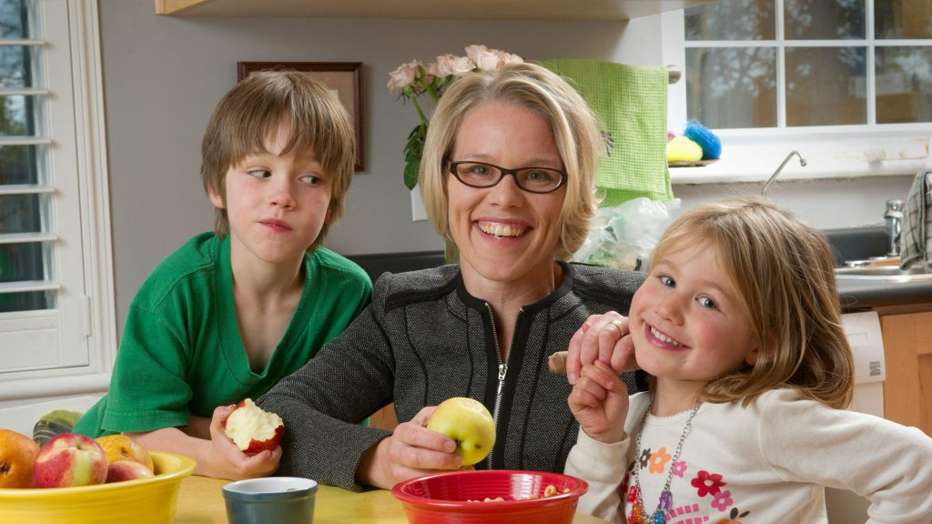A mother and her children pose at a kitchen table.