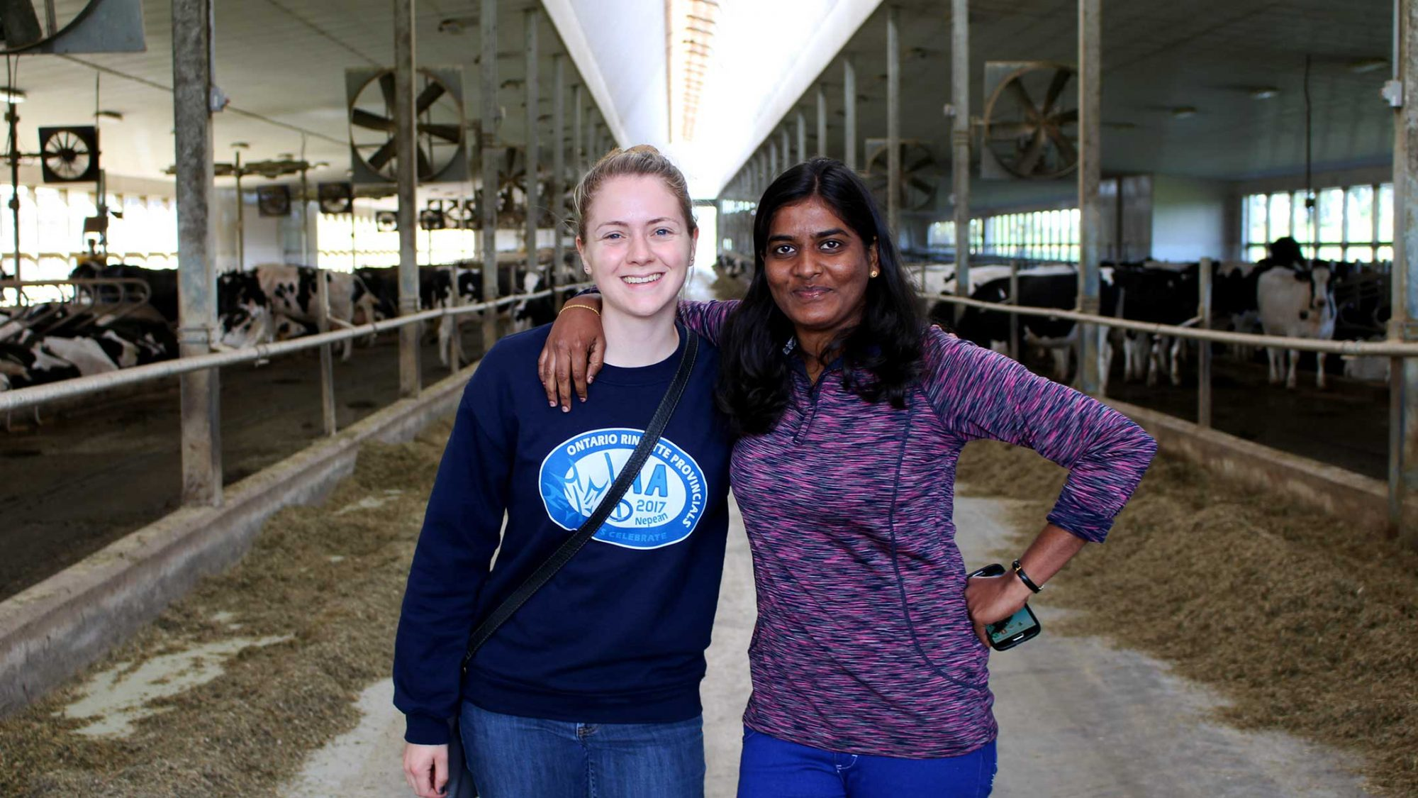 Two graduate students stand in a dairy barn