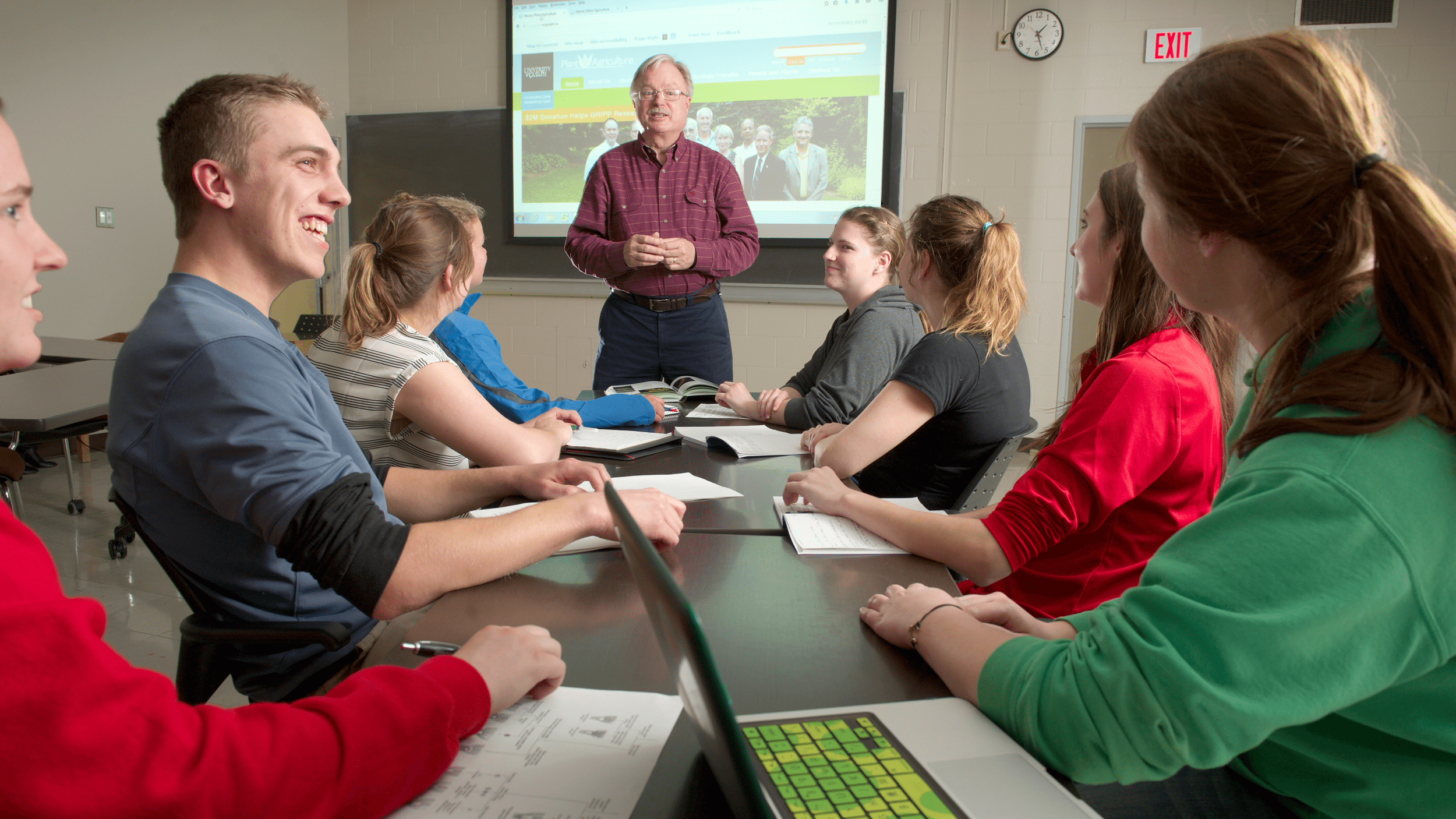 Students sit at a table listening to professor, with a website projected on a screen behind him