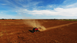 Red combine in a brown field with a bright blue sky