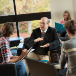 Professor and chats with students sitting in chairs