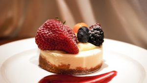 A cheesecake dessert with fruit on a white plate