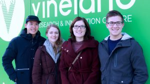 Four students stand in front of green sign at greenhouse