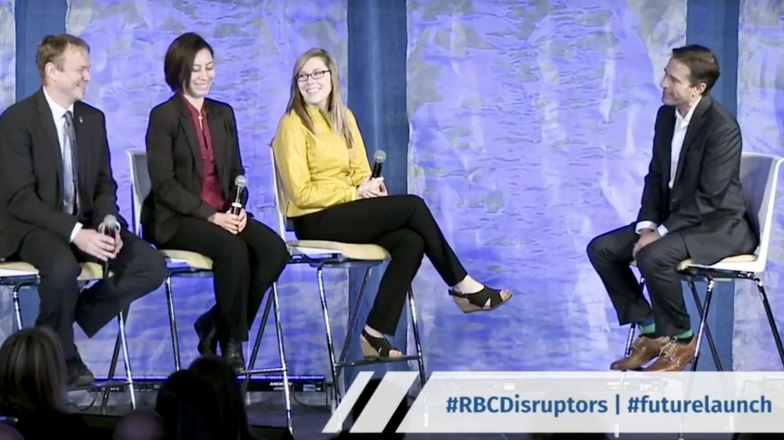 Evan, Leah and Amberley on stage with John Stackhouse with RBC graphic over
