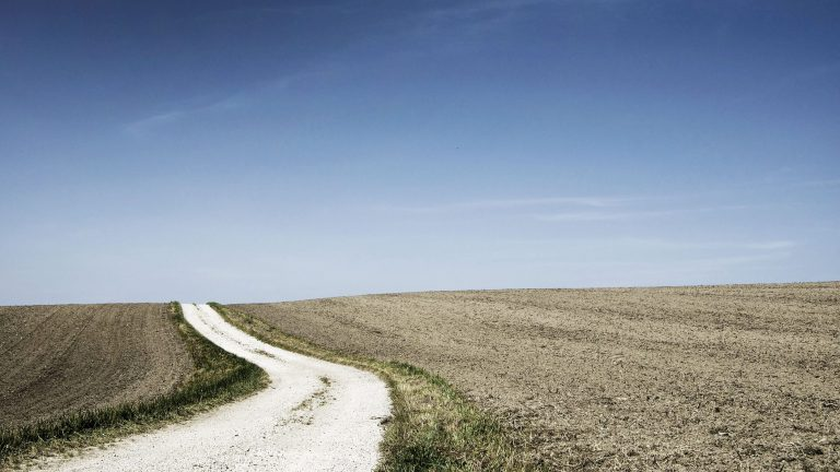 A dirt road runs through a bare field under a blue sky