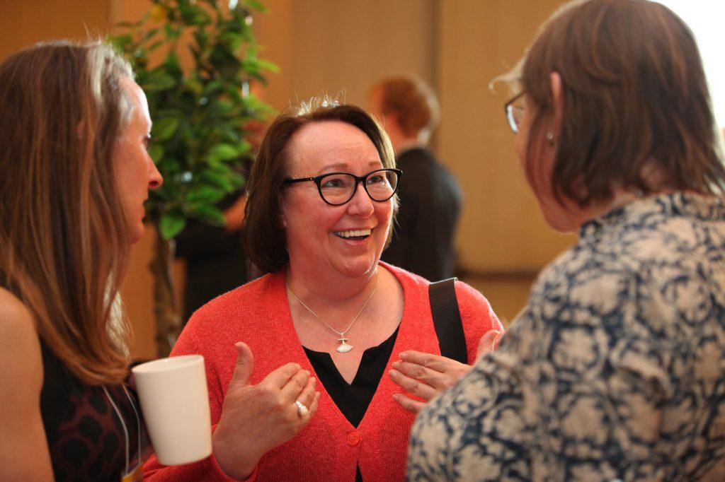 Sheila Watt-Cloutier speaks to two women at a meeting.