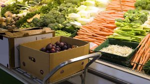 A cart with produce from Canada in boxes sits in front of produce shelves