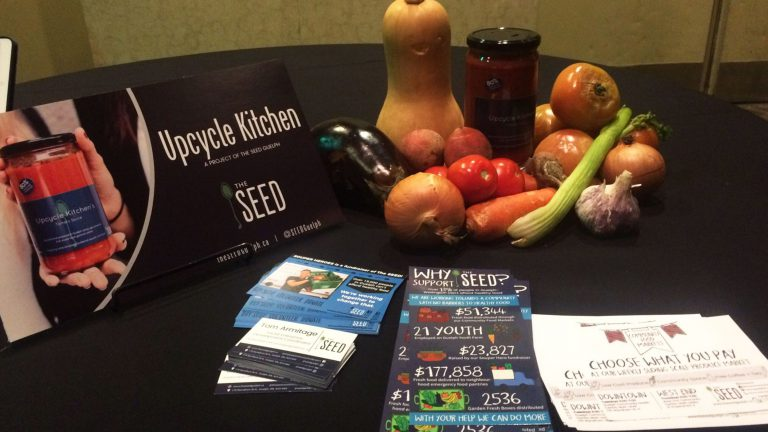 Fliers for the Seed and some vegetables sit on a table