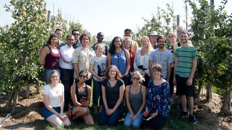 Group of students poses in apple orchard