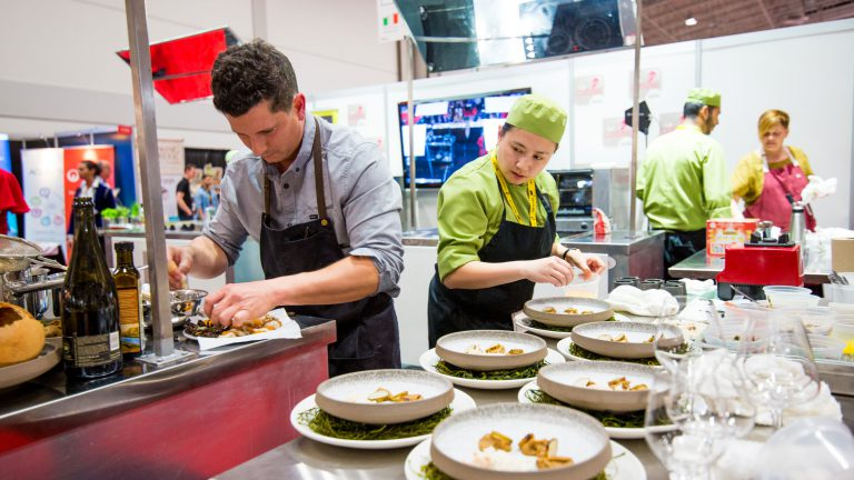 Chef Pierre plates food while his assistant looks on.
