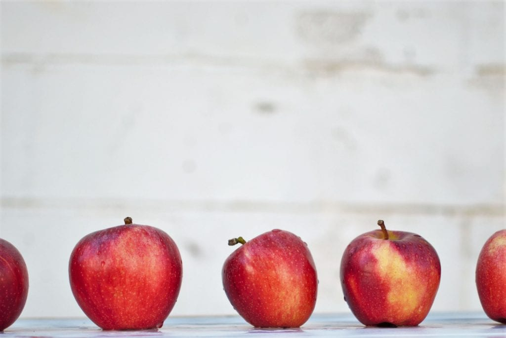 5 red apples lined up on a white surface