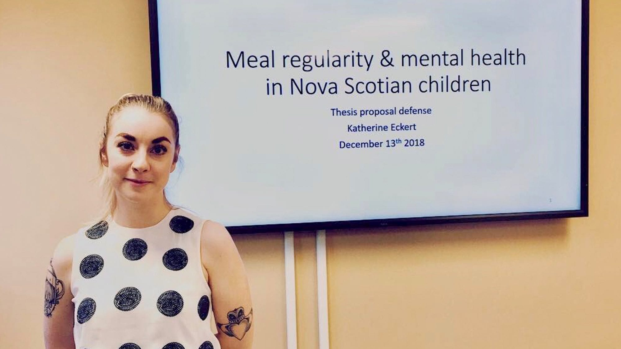 "Katherine poses in front of screen showing the title of her presentation, ""Meal regularity and mental health in Nova Scotian children"""