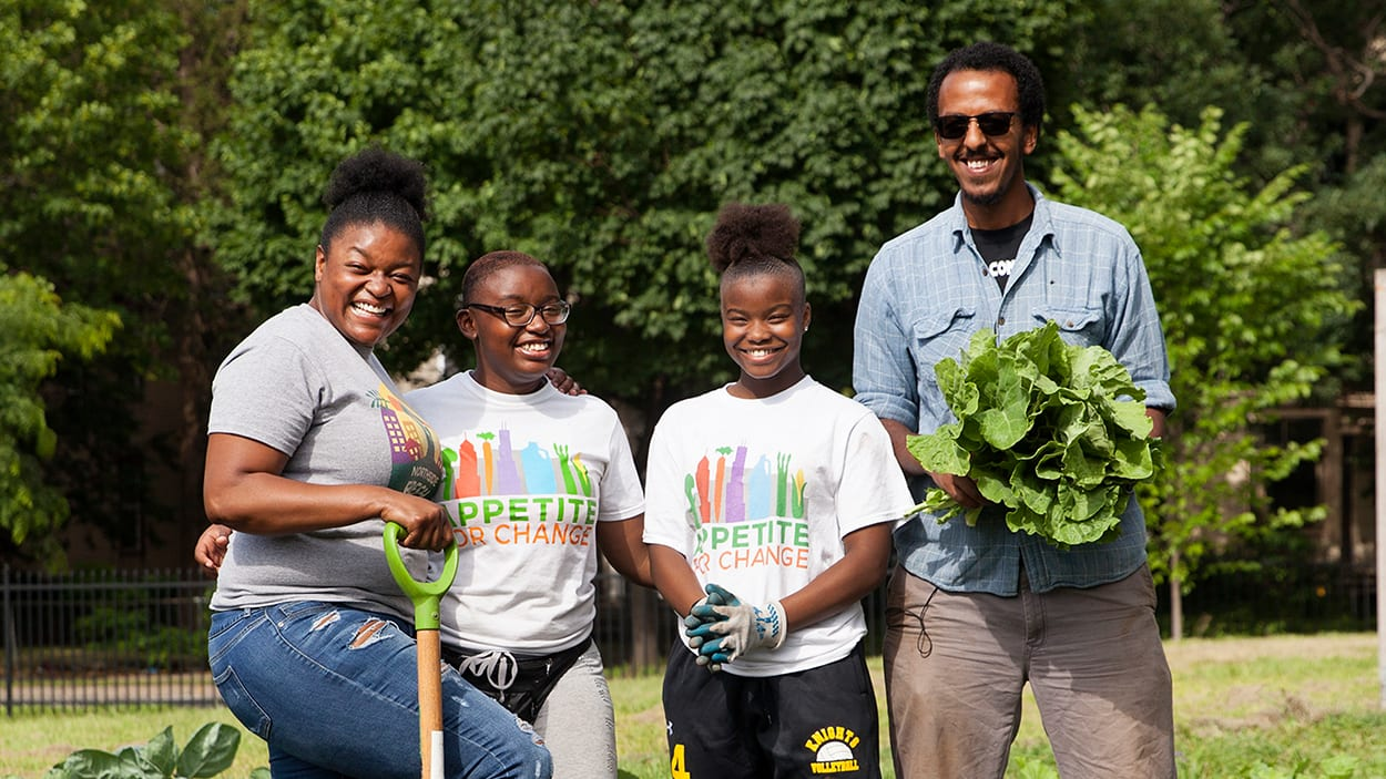 A group of adults and children pose with vegetables and garden tools.