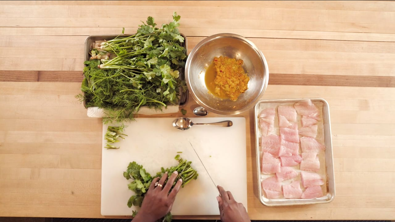 Chef Suzanne Barr chops cilantro on a counter surrounded by other ingredients.
